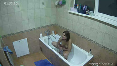 Cute medium boobed teen brunette is squatting in the bath and rubbing her shaved cunt