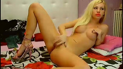 Blonde slut is undressing and hotly posing to the webcam and masturbating shaved pussy