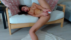 Exciting hot young brown haired Lionali is pleasantly masturbating her cunt with dildo