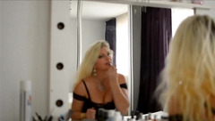 Incredibly hot blonde milf LeilaHot69 in black sexy dress and nylon stockings is doing make up