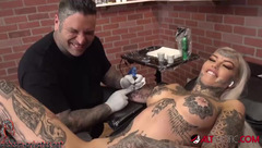 Blonde is being tattooed allover her body and being drilled in shaved cunt with vibrator dildo