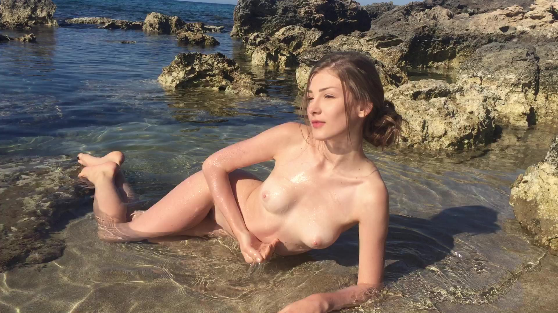 Skinny blonde Fressia is lying nude on the beach and stroking her shaved cunt