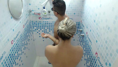 Strong and sexy shaped young dude is washing in shower before hot blonde joins him
